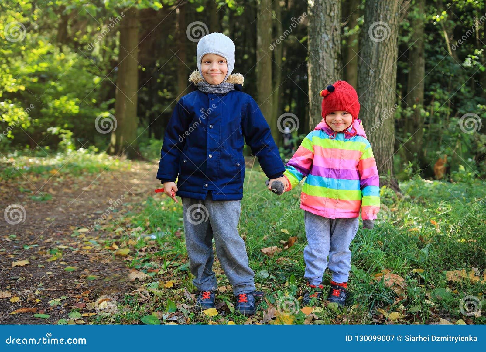 Kamratskap för barn` s Barn står tillsammans och rymmer händer i hösten parkerar Pys- och flickavänner