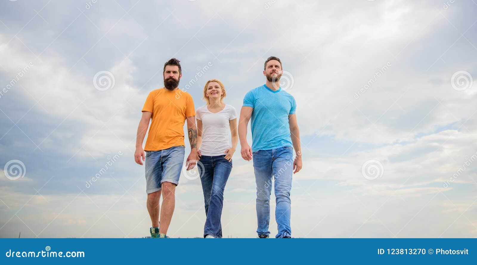 Kamratskap som testas för år Riktiga vänner för enig threesome Män och kvinnan går dramatisk bakgrund för molnig himmel riktigt
