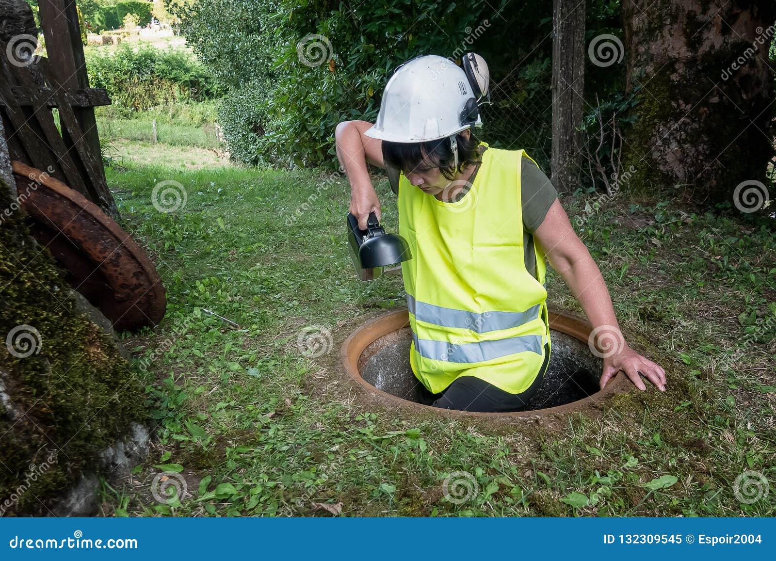 Kanał ściekowy naprawa pracuje w manhole kobieta pracownikiem