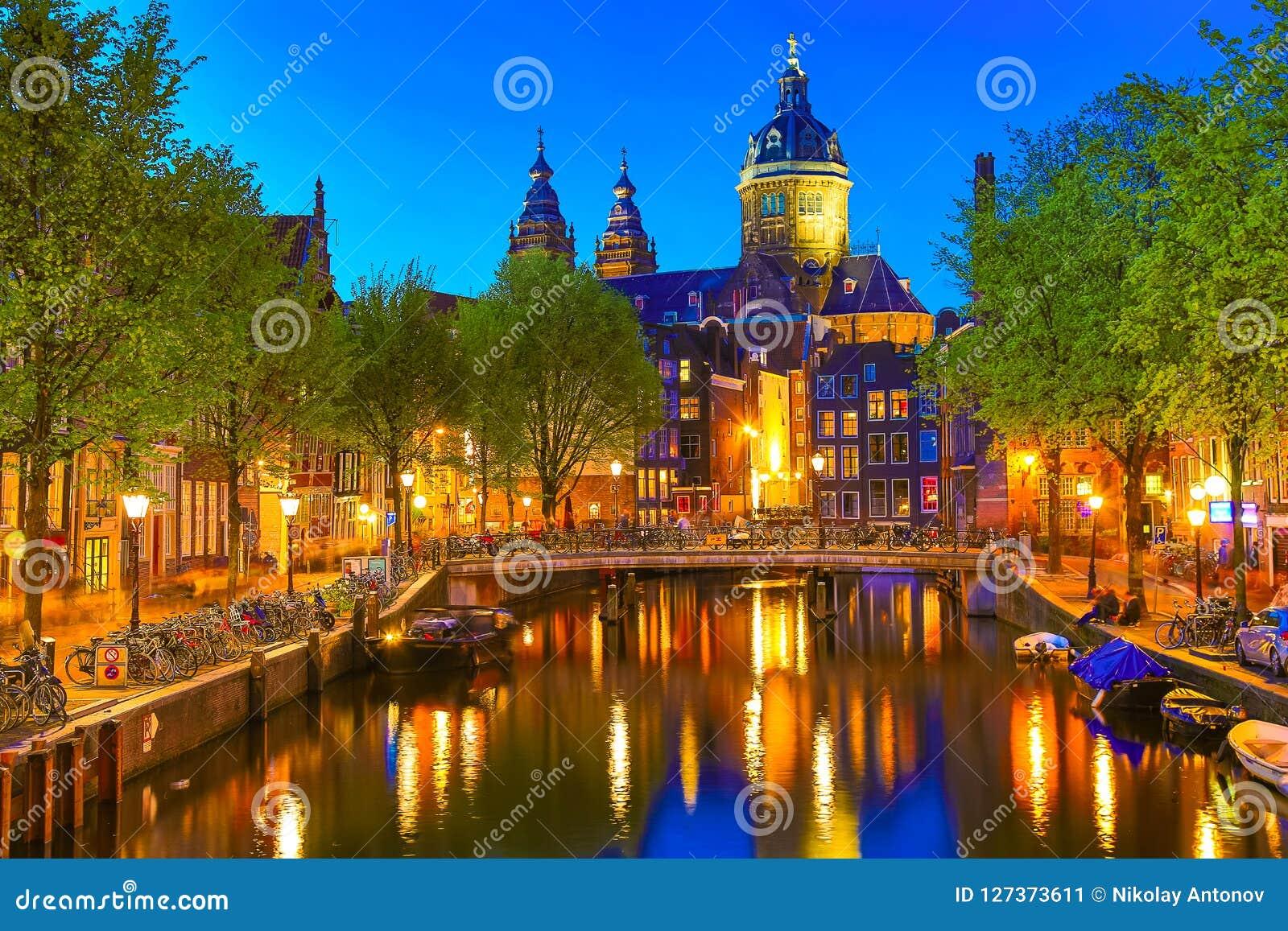 Kanaal en St Nicholas Church in Amsterdam bij schemering, Nederland Het beroemde oriëntatiepunt van Amsterdam dichtbij Centrale P
