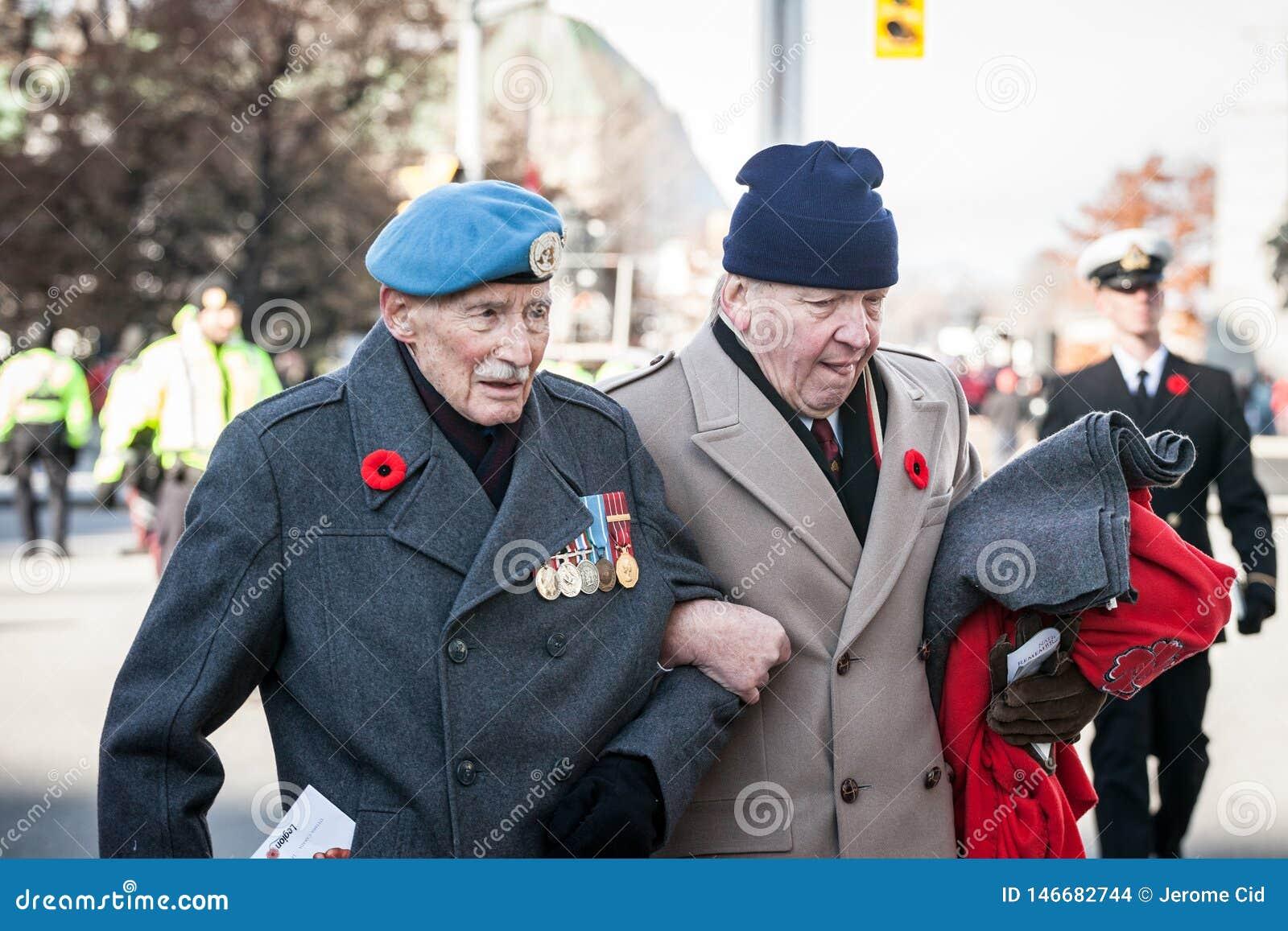 Kanadensisk krigsveteran för armé två, höga män, med deras medaljer och minnevallmo som betalar respekter till döda soldater