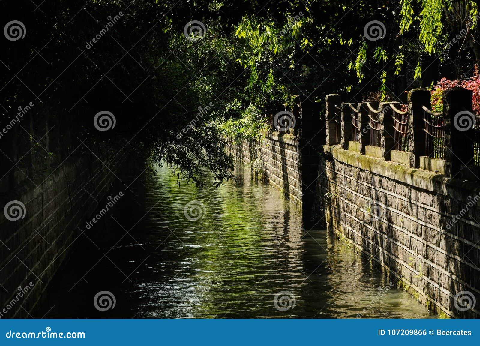 Kanal med stenbalustrader i träig stad av den soliga vårmornien