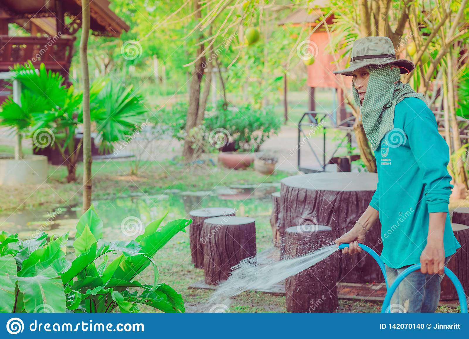 KANCHANABURI-THAILAND, March 2, 2019 : Unidentified Senior man watering plants with hose and working in garden at his home on