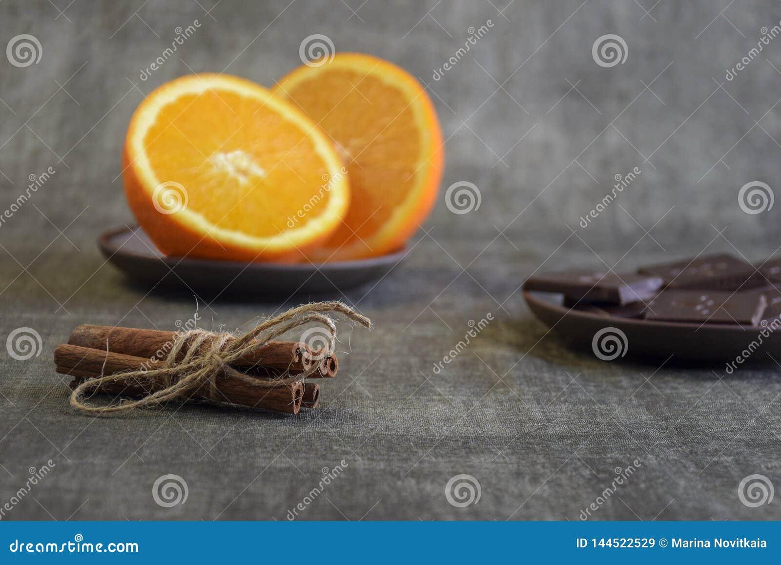 Kanelbruna pinnar, skivad apelsin och stycken av mörk choklad