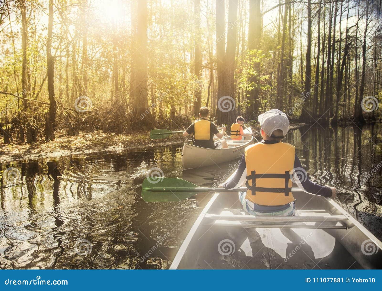 Kanota ner den härliga floden i en cypressskog