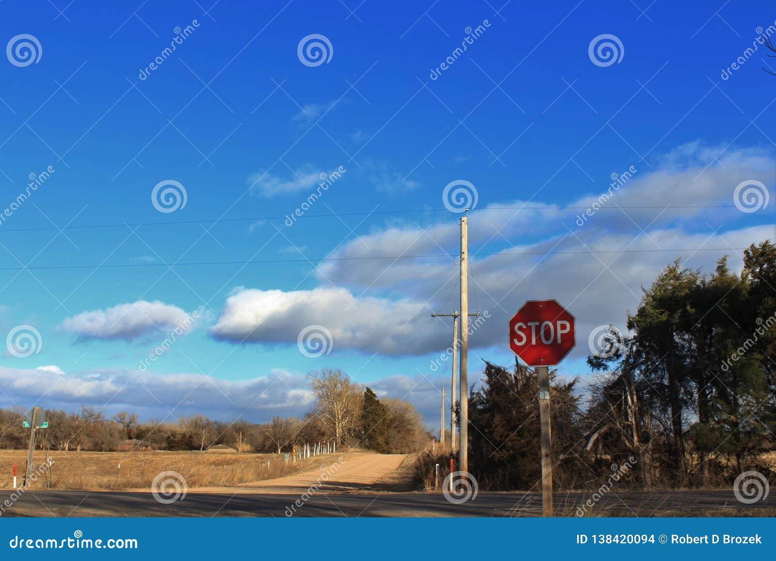 Kansas-Land-Straße mit blauem Himmel, Wolken und einem Stoppschild