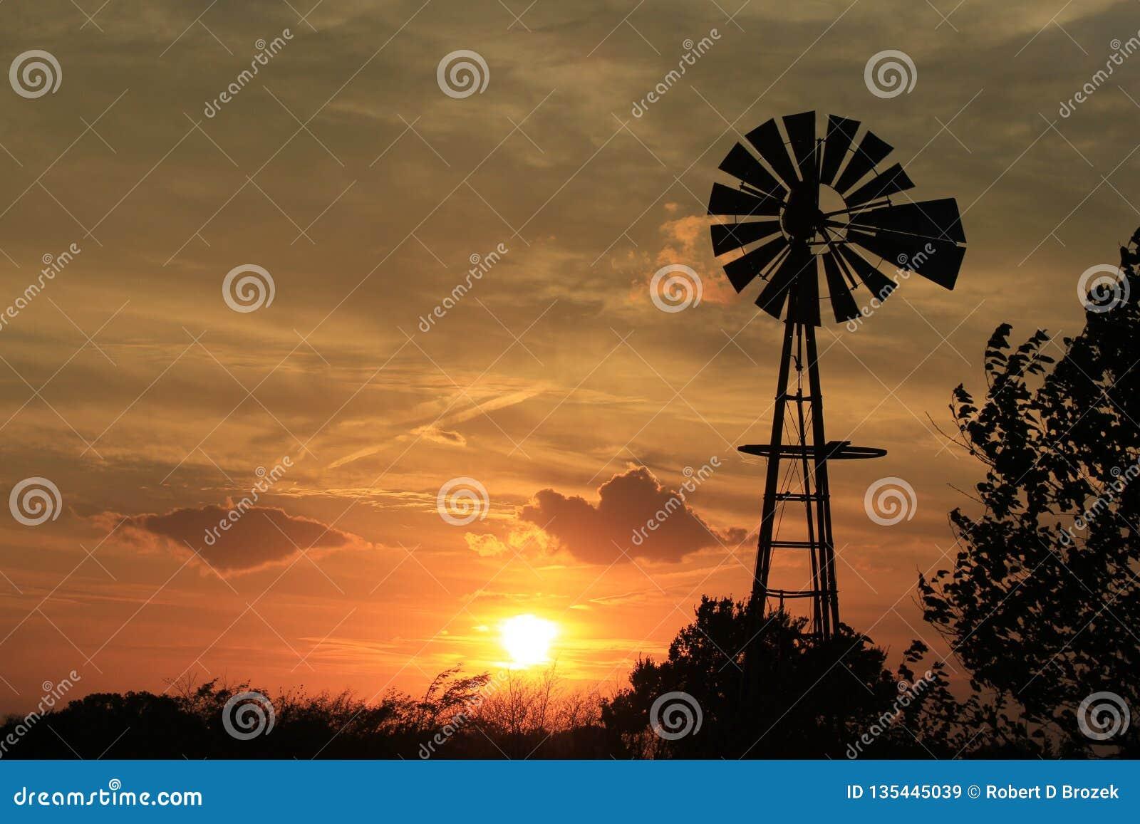 Kansas-Sonnenuntergang-Windmühle mit grauem Himmel und weißen Wolken