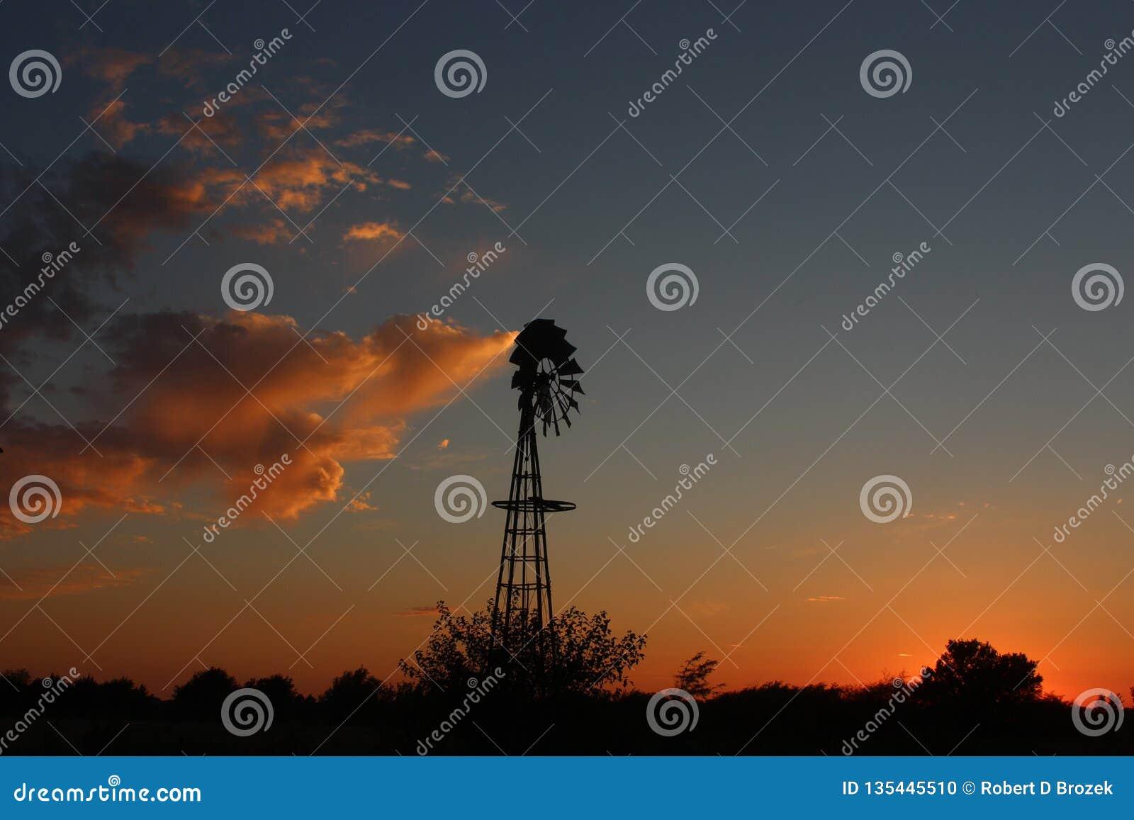 Kansas-Windmühlen-Sonnenuntergang mit den hellen und bunten Wolken heraus im Land