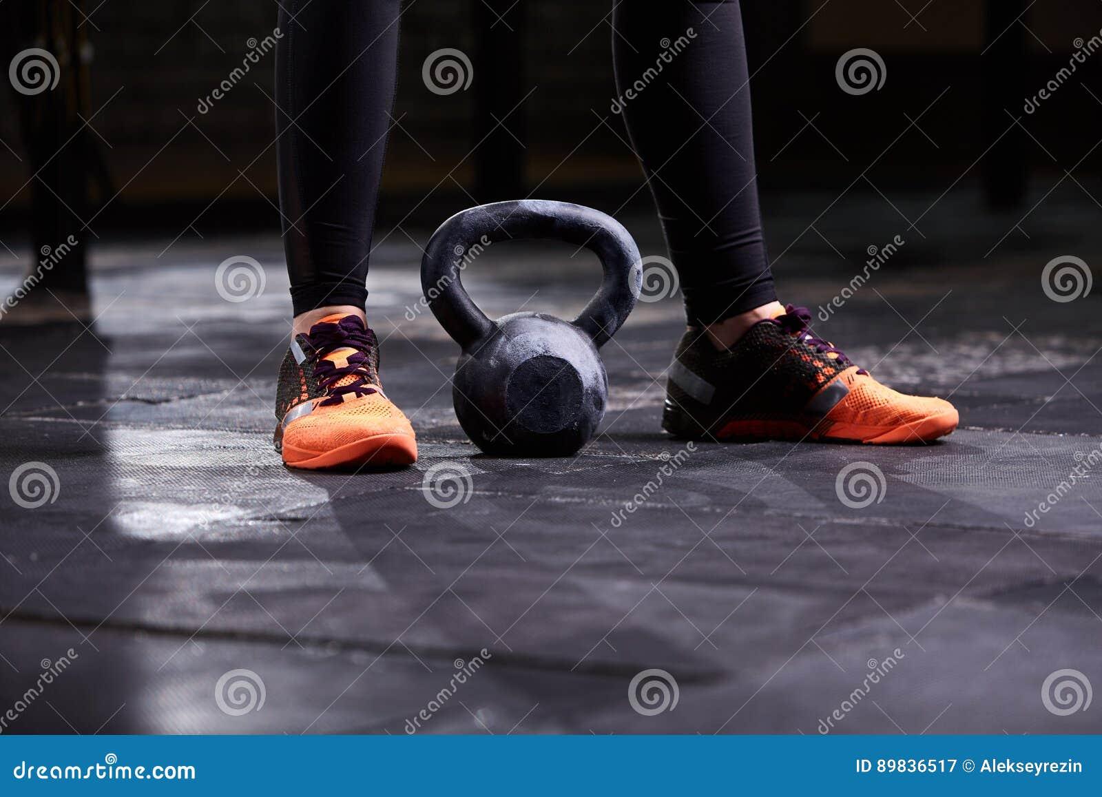 Kantjusterad bild av den unga kvinnan, ben i den svarta damasker, orange gymnastikskor och kettlebell Crossfit genomkörare