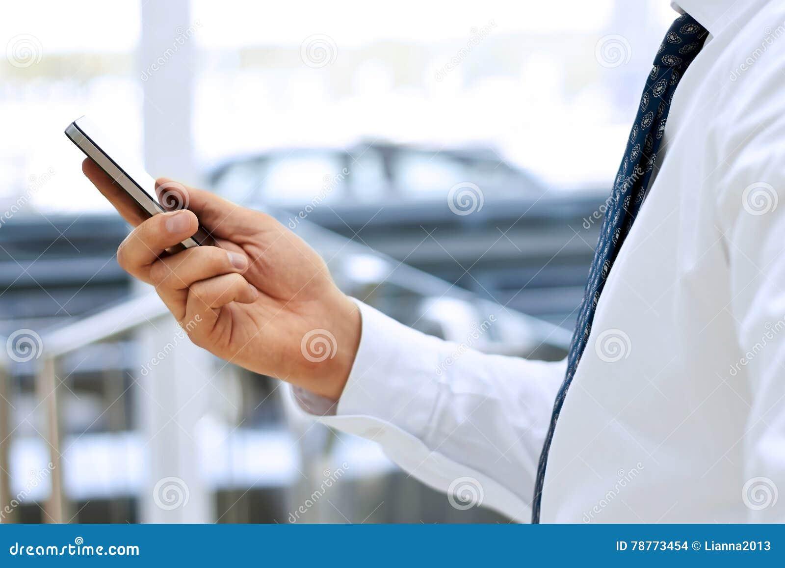 Kantjusterad sikt av affärsmannen som rymmer mobiltelefonen som framme står fönstret