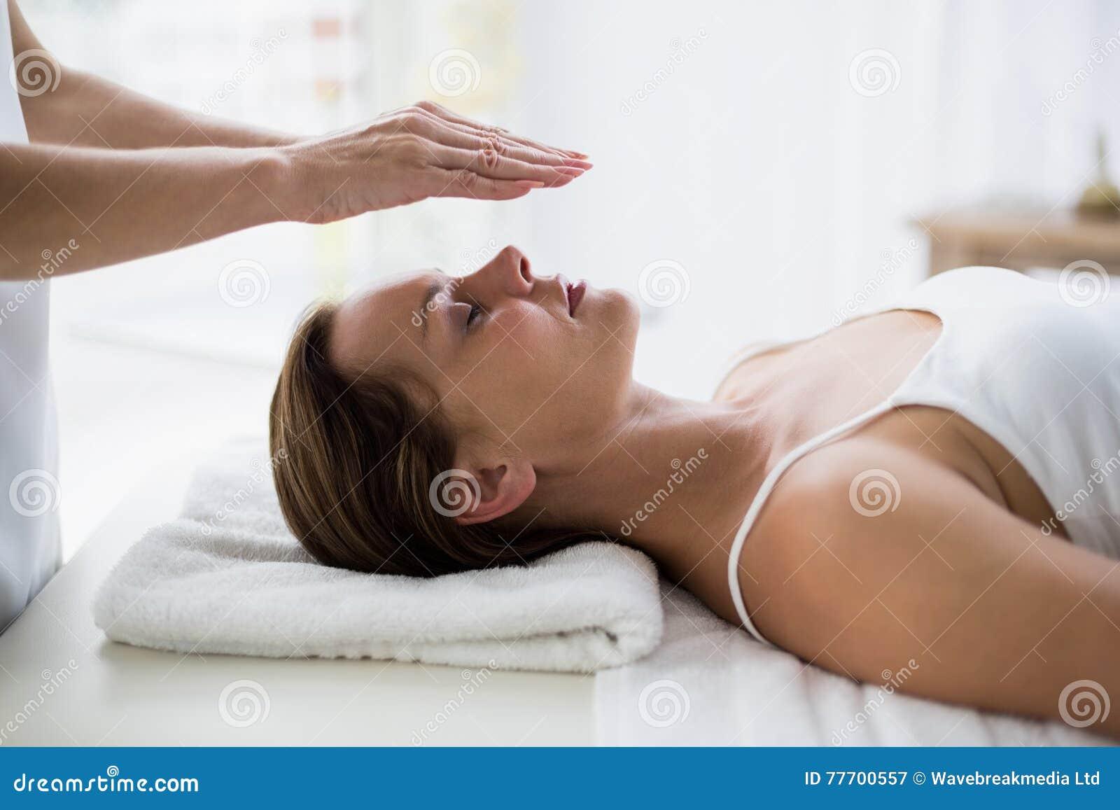 Kantjusterade händer av den utförande reikien för terapeut på kvinna