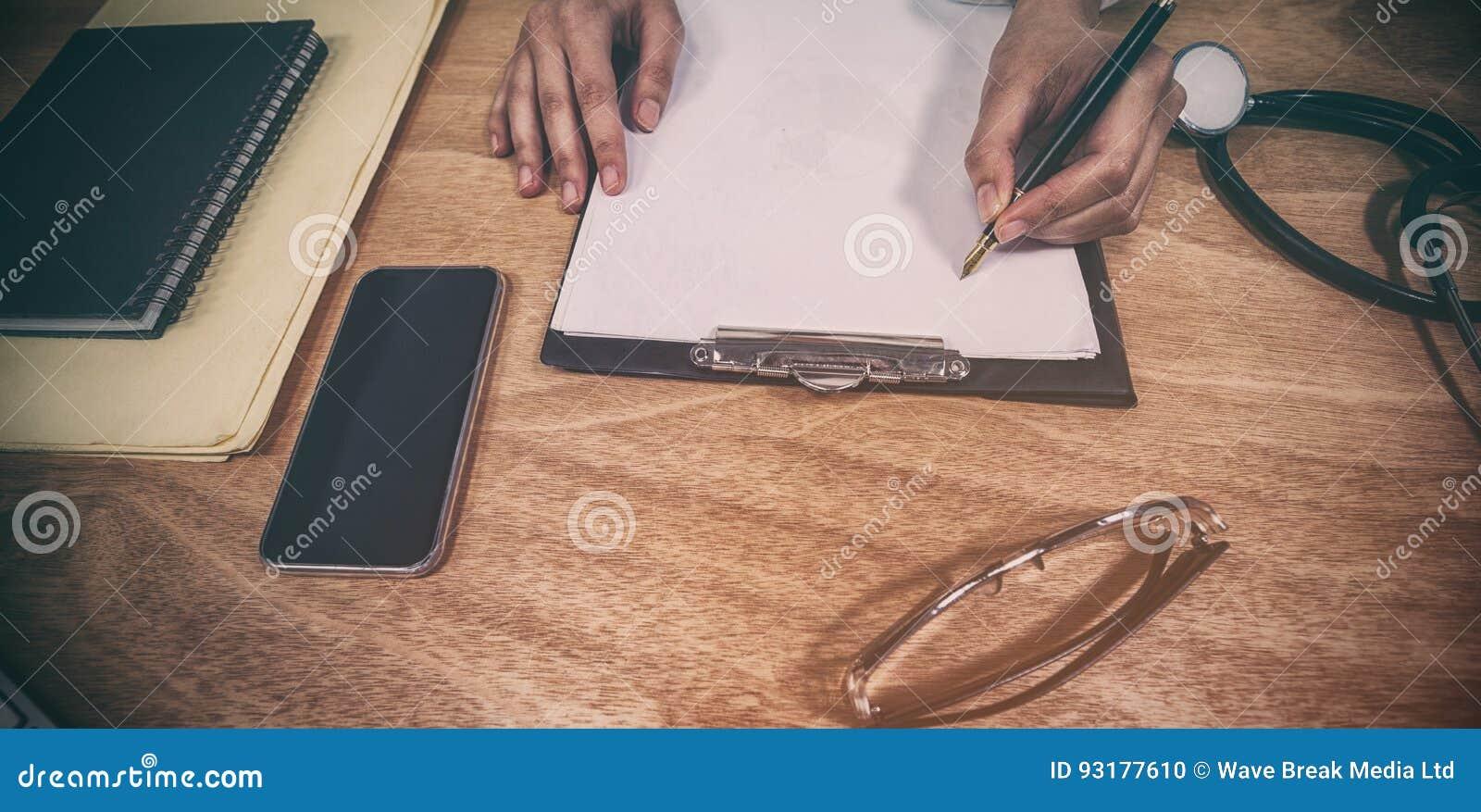 Kantjusterade händer av doktorshandstilreceptet på skrivplattan på skrivbordet