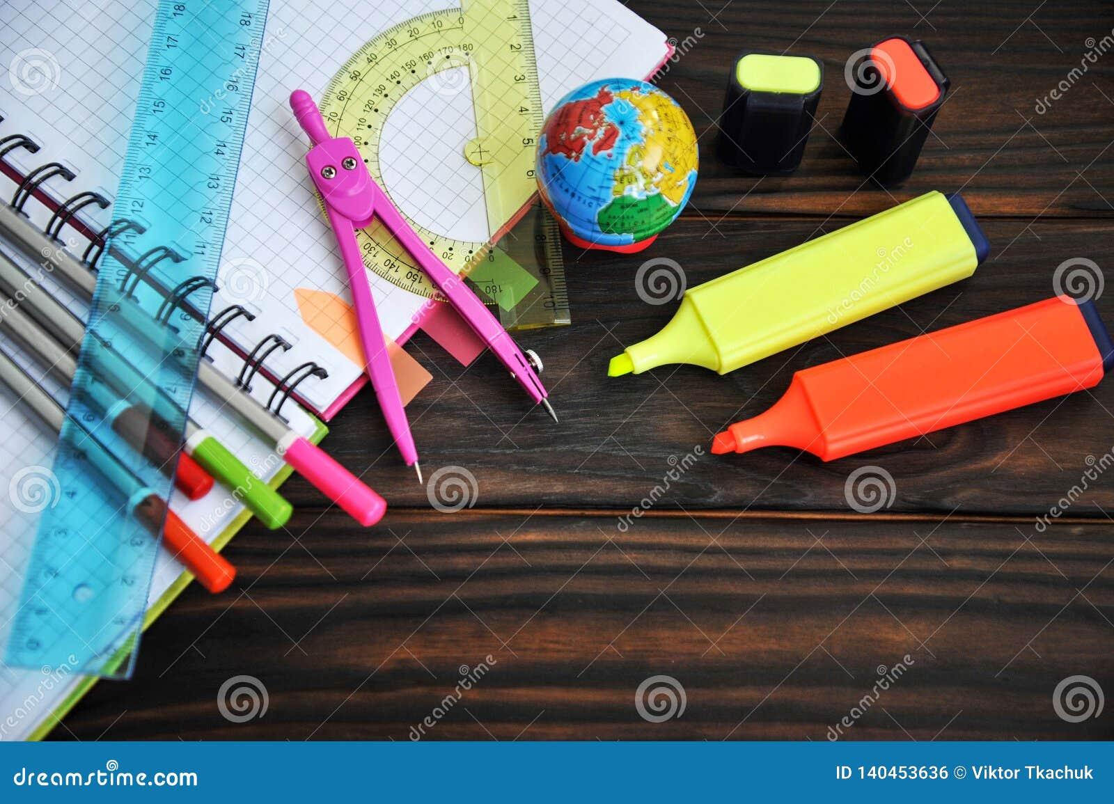 Kantoorbehoeften op een notitieboekje wordt verspreid die op een houten lijst liggen die