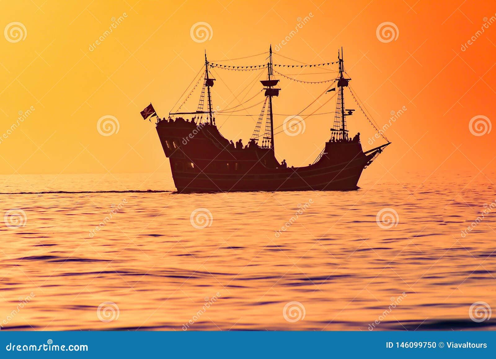 Kapitan notatki pirata rejs na kolorowym zmierzchu tle w zatoki wybrze?u Wyrzuca? na brzeg