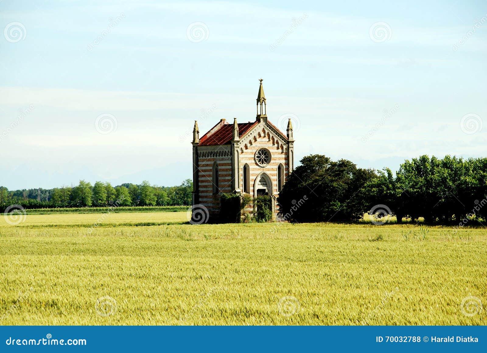 Kaplica w kukurydzanym polu obok drzew zbliża comacchio w Italy