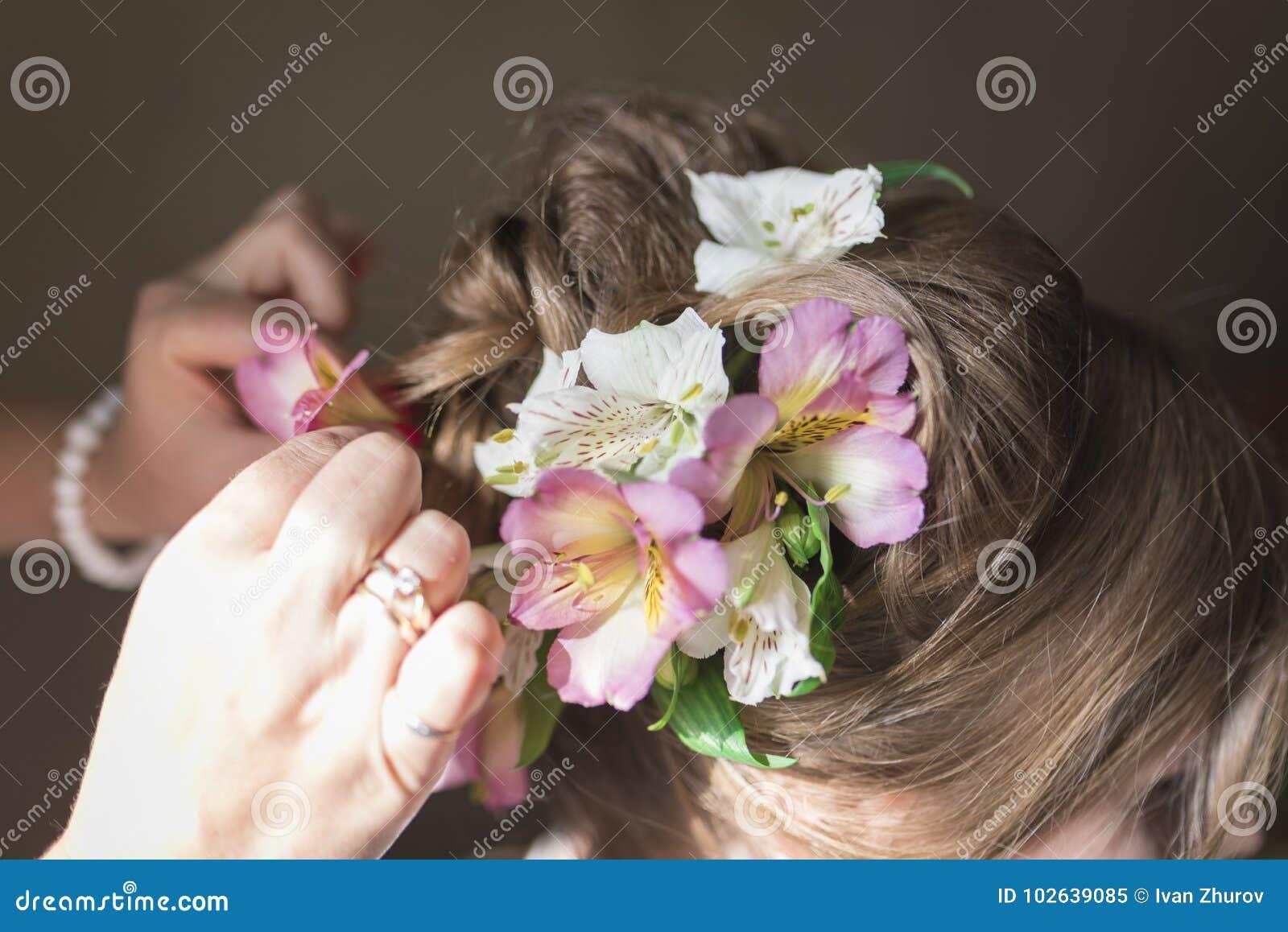 Kapper die een huwelijkskapsel met verse bloemen doen