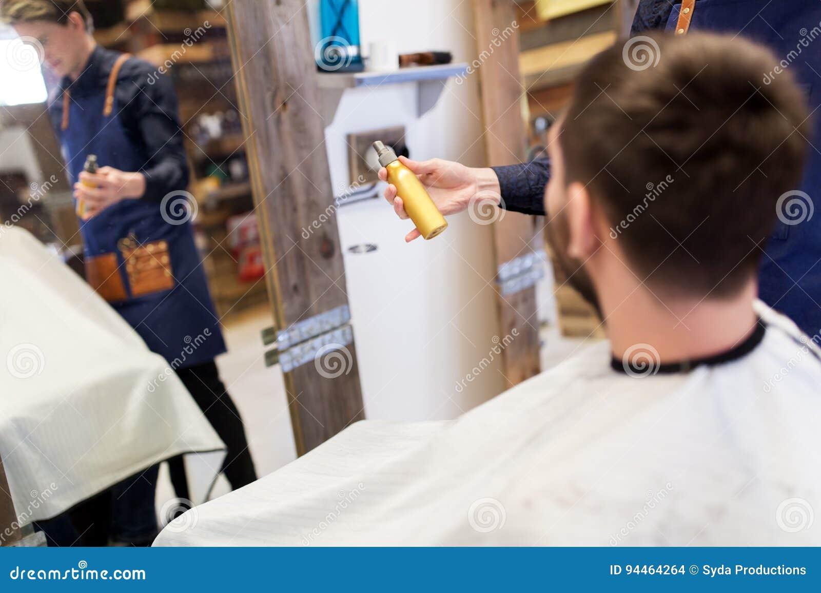 Kapper die haar het stileren nevel tonen aan mannelijke klant