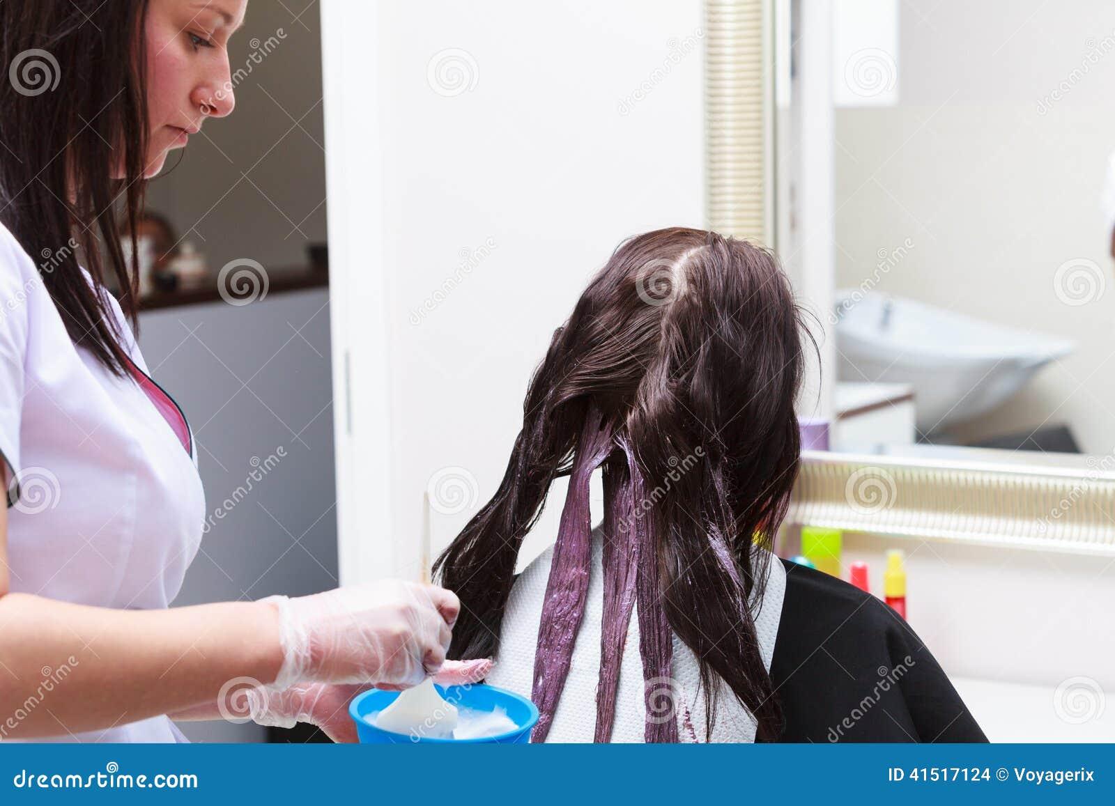 Kapper die kleuren vrouwelijke klant toepassen bij salon, die haarverf doen