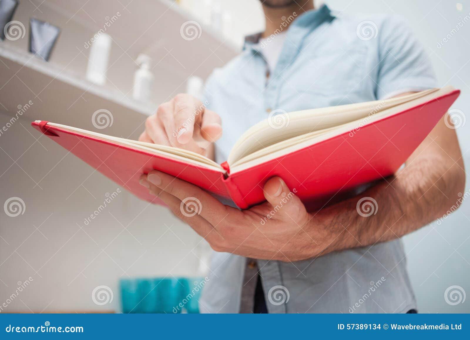 Kapper met voorraadboek op het werk