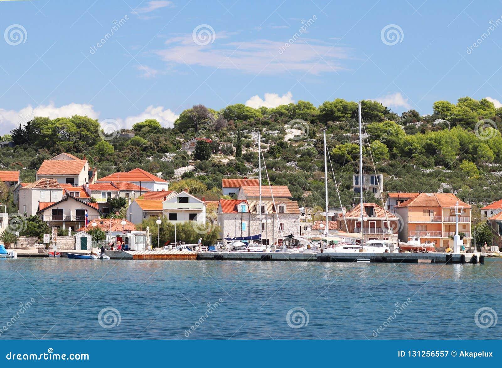 Kaprije, Chorwacja, Europa - 7 9 2018: Bulwar mały Chorwacki miasteczko w Adriatyckim morzu Żeglowanie jacht na tle t