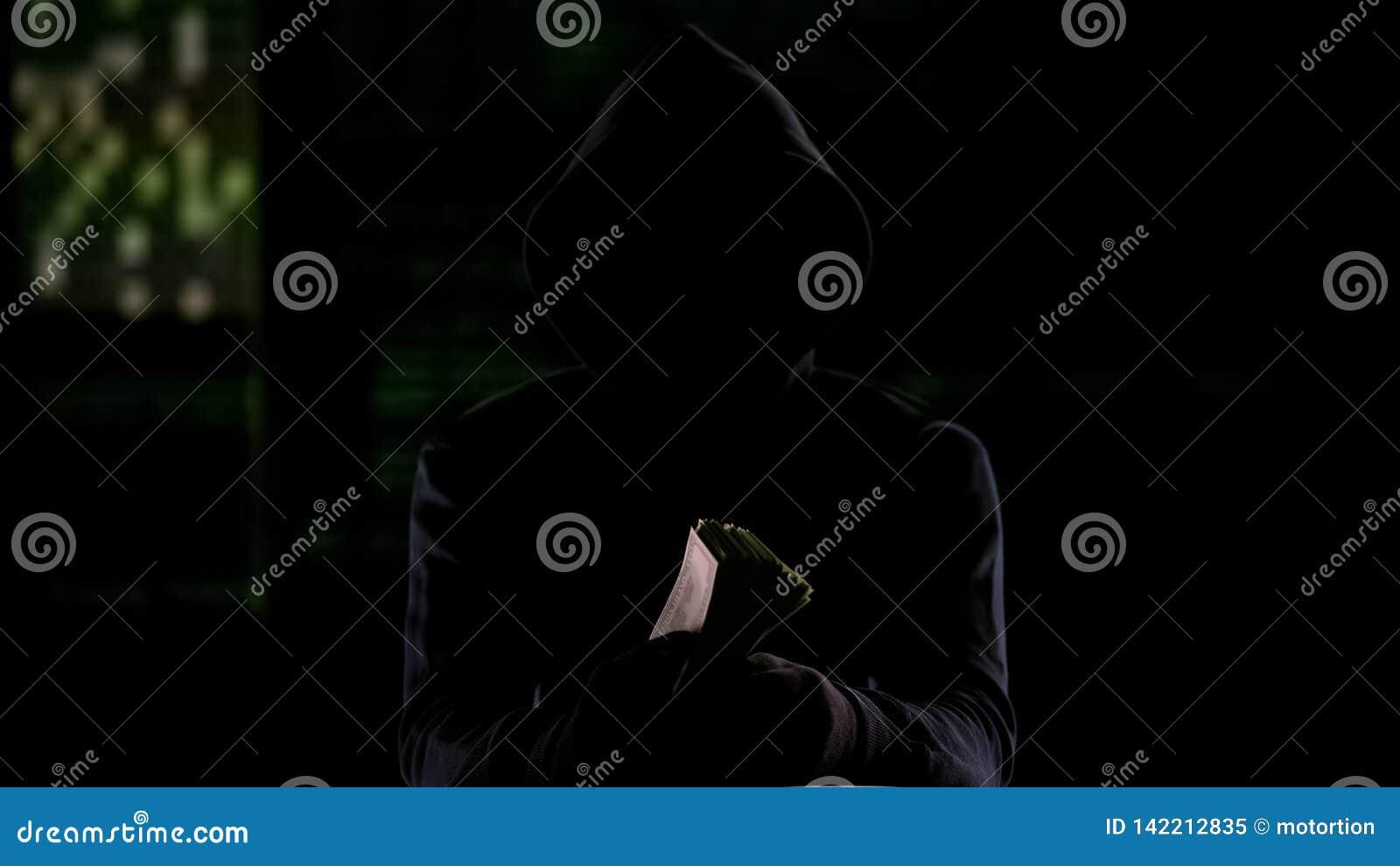 Kapturzasty mężczyzna w ciemności mienia gotówce, dzierżawienie nagrodzie lub skradzionym pieniądze,