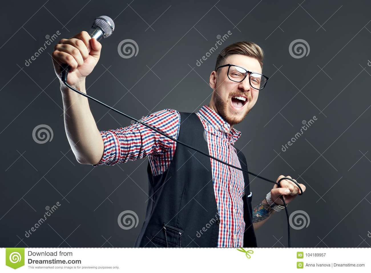 Karaoke man sings the song to microphone, singer with beard on grey background. Funny man in glasses holding a microphone