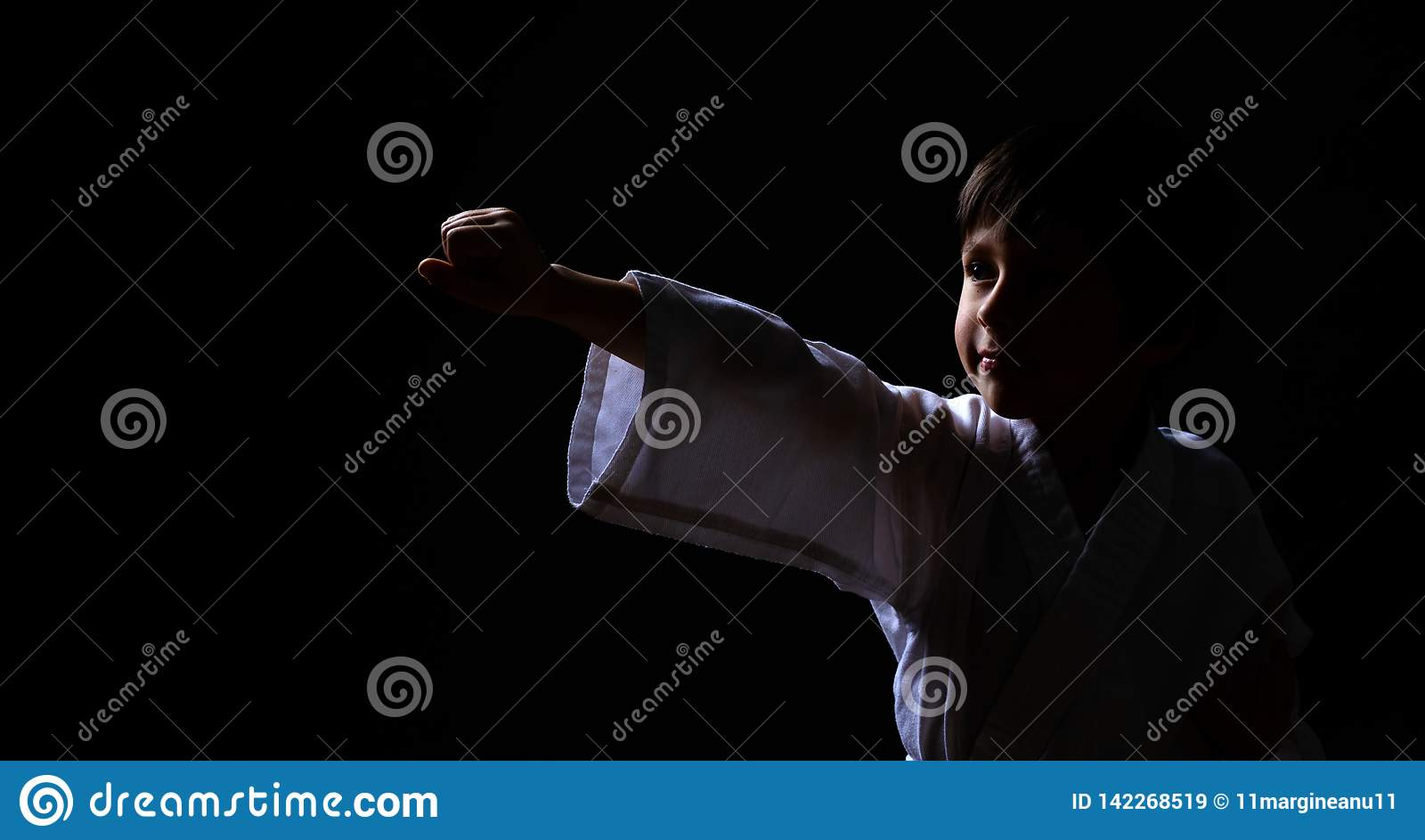 A karate boy in white kimono posing on dark background. Child ready for martial arts fight. Kid fighting at Aikido training. Best