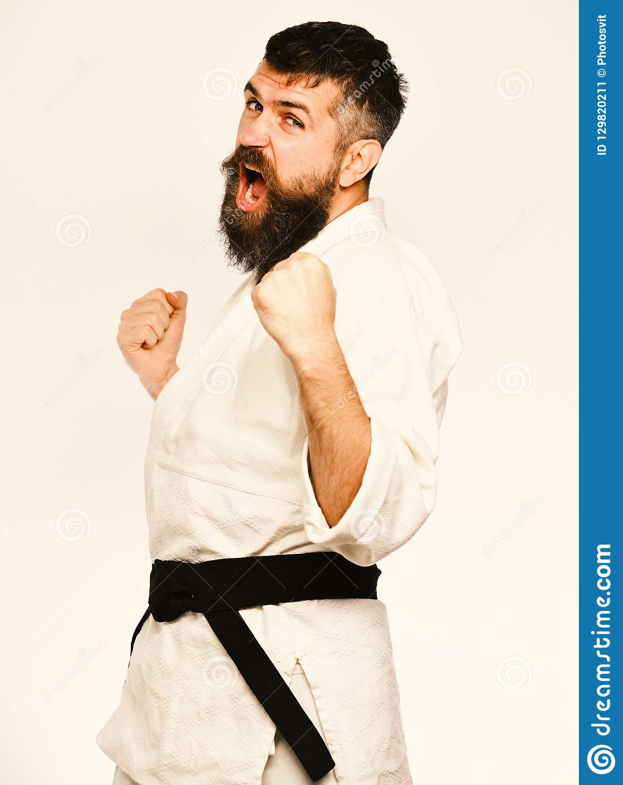 Karate man with angry face in uniform. Man with beard