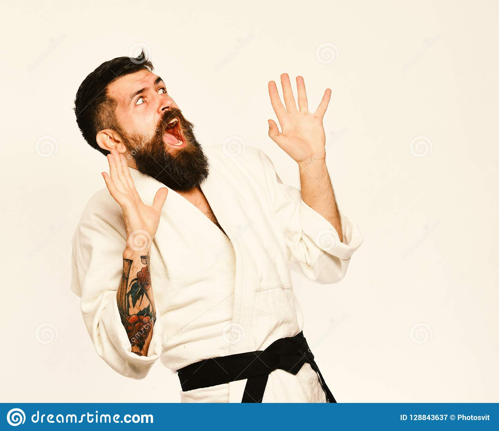 Karate man with scared face in uniform. Man with beard