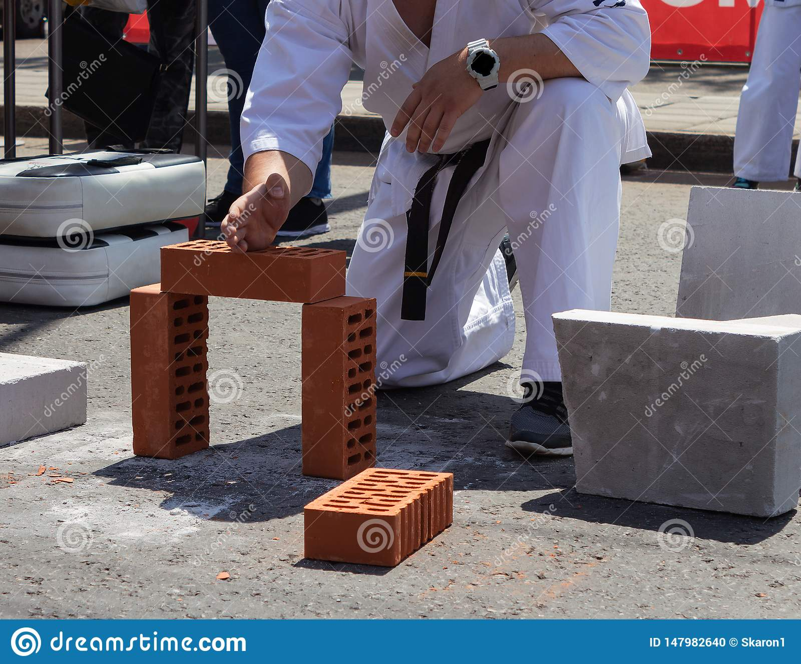 Karate player at a sporting event breaks a brick with his hand