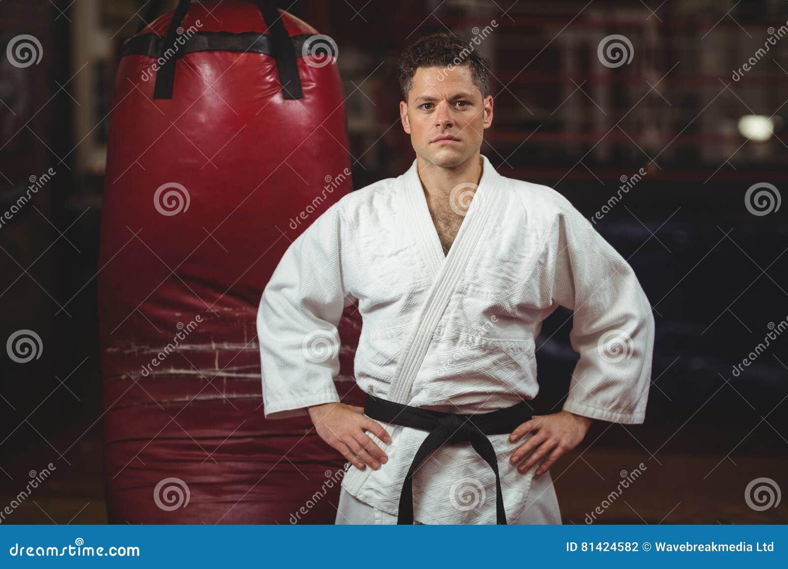 Karatespeler met handen op heupen die zich in geschiktheidsstudio bevinden