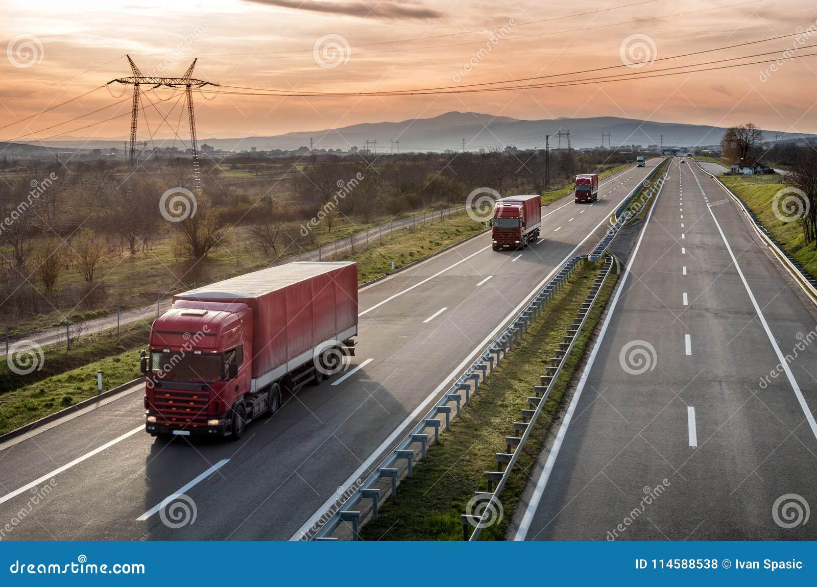Karawana Czerwona ciężarówka przewozi samochodem na autostradzie