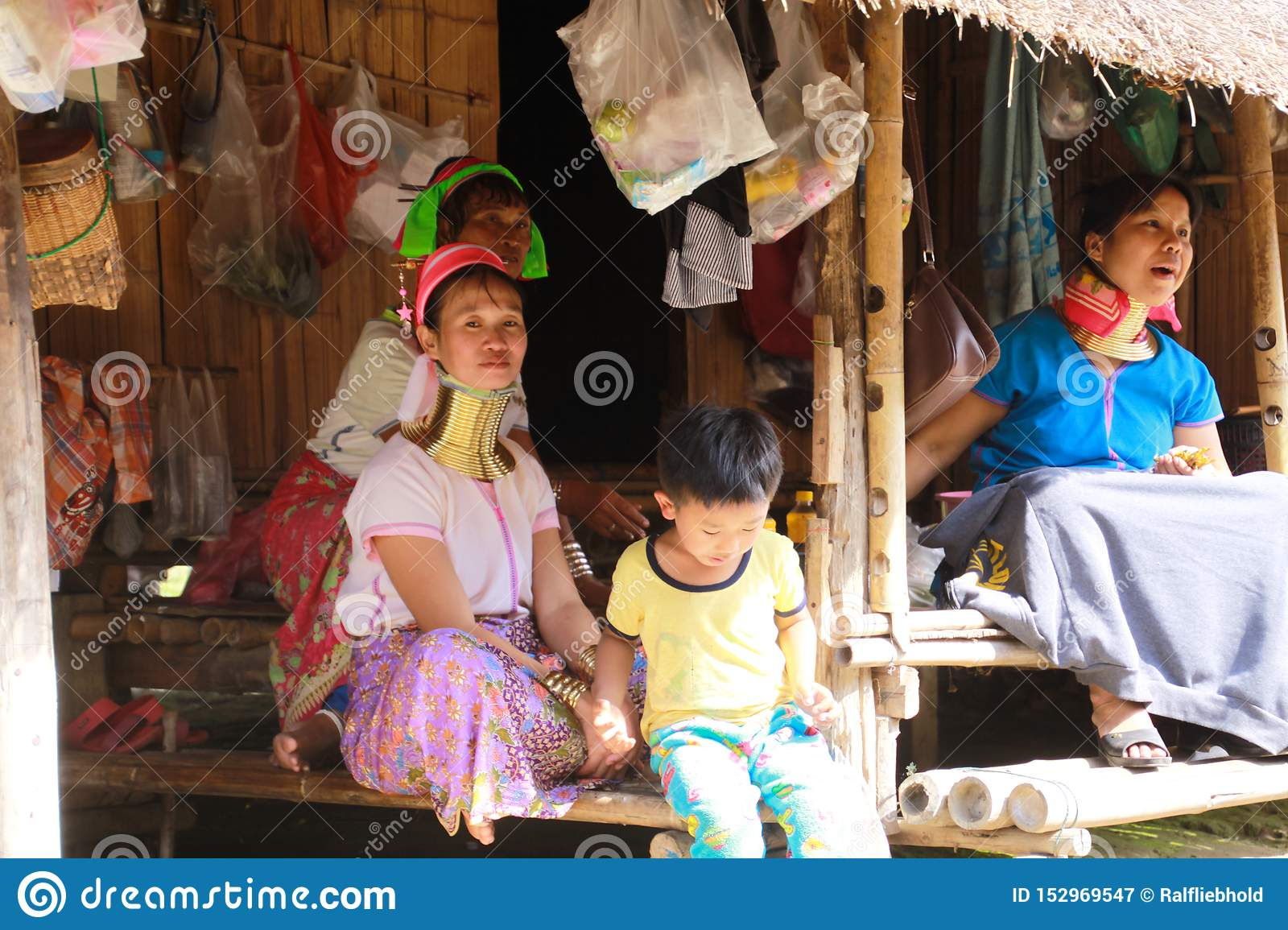 LONGNECK KAREN VILLAGE, THAILAND - DECEMBER 17. 2017: Long neck family sitting in front of a bamboo hut