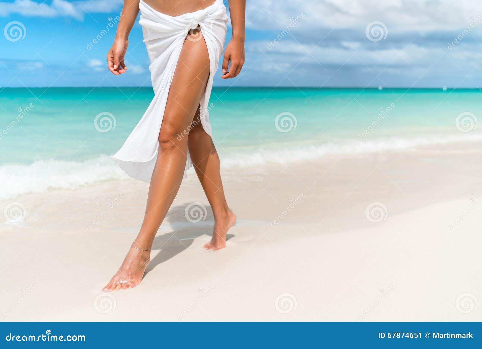 Karibiskt strandlopp - kvinnan lägger benen på ryggen closeupen som går på sand