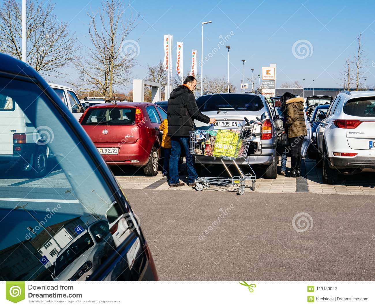 Family shopping for food in Kaufland supermarket parking