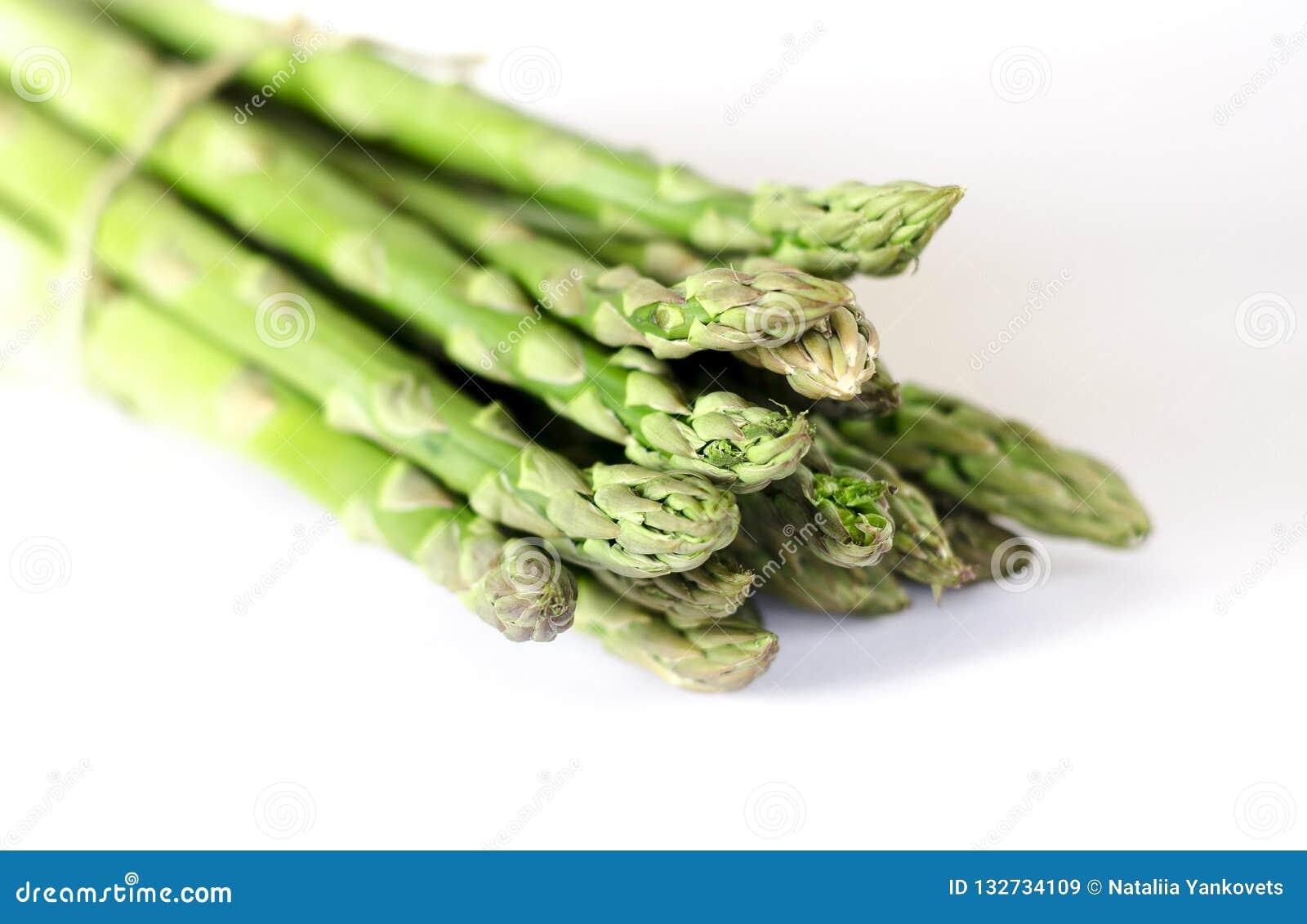 Karmowego tła szparagowego mieszkania nieatutowy wzór wiązka świeży zielony asparagus na białym tle, odgórny widok