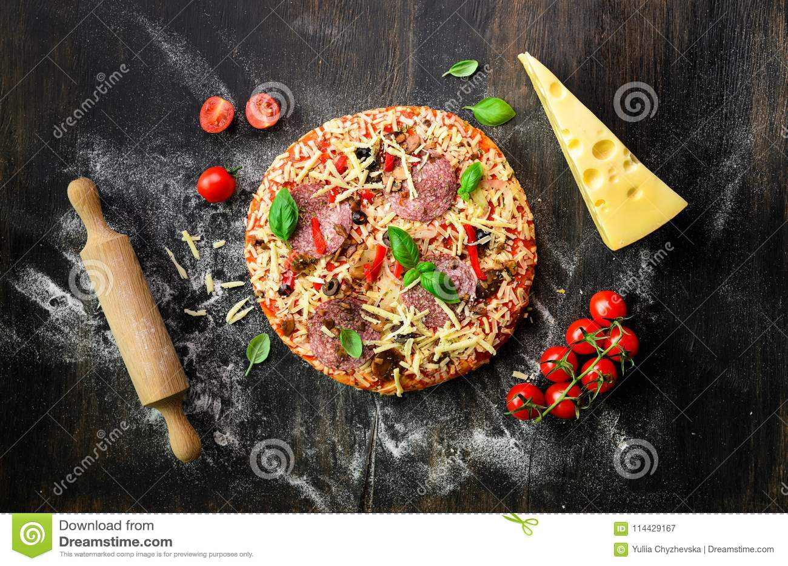 Karmowi składniki dla włoskiej pizzy, czereśniowi pomidory, mąka, ser, basil, toczna szpilka, pikantność na ciemnym tle wierzchoł