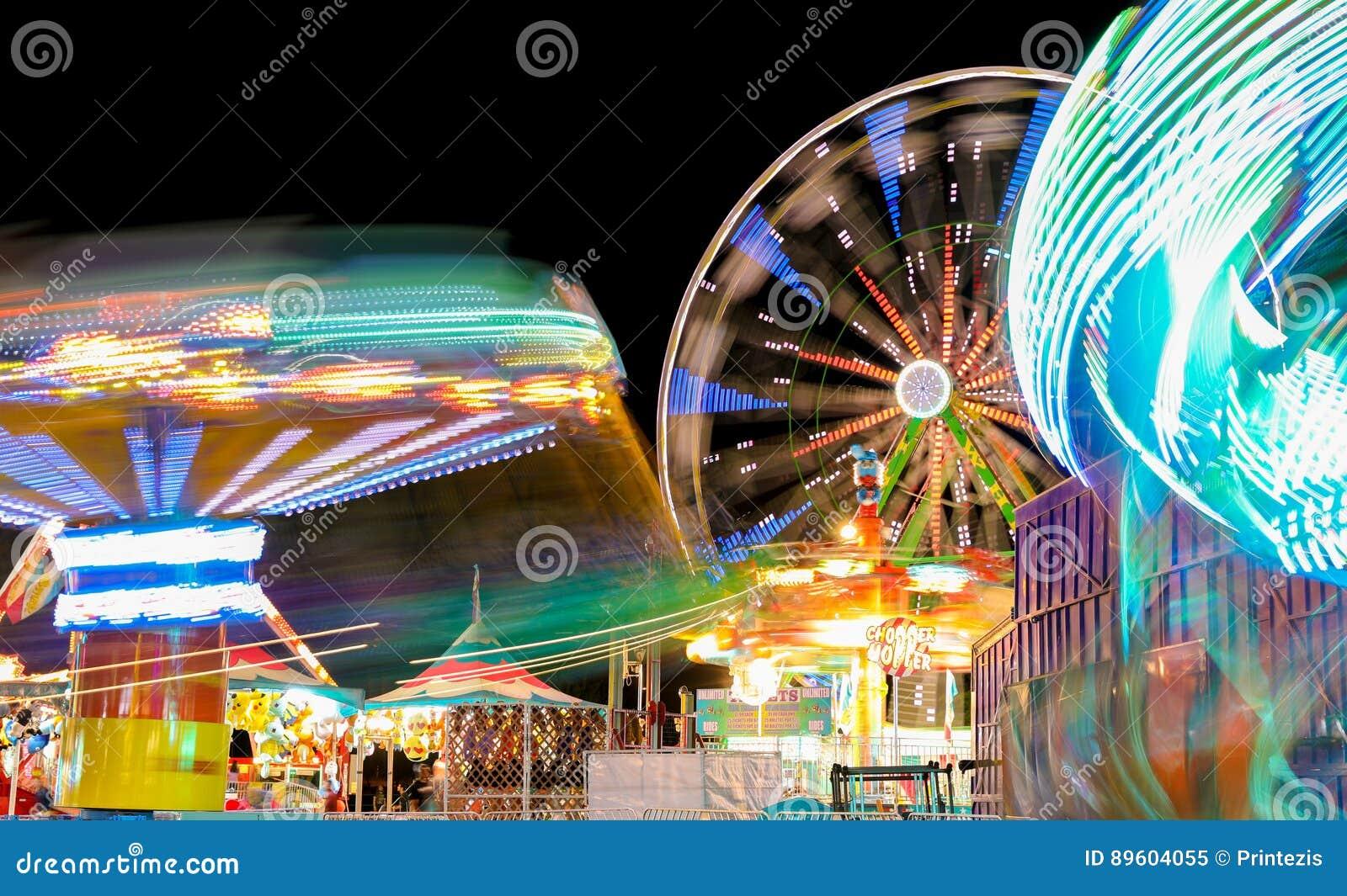 Karnawał i Ferris koło przy nocy przędzalnictwa światłami