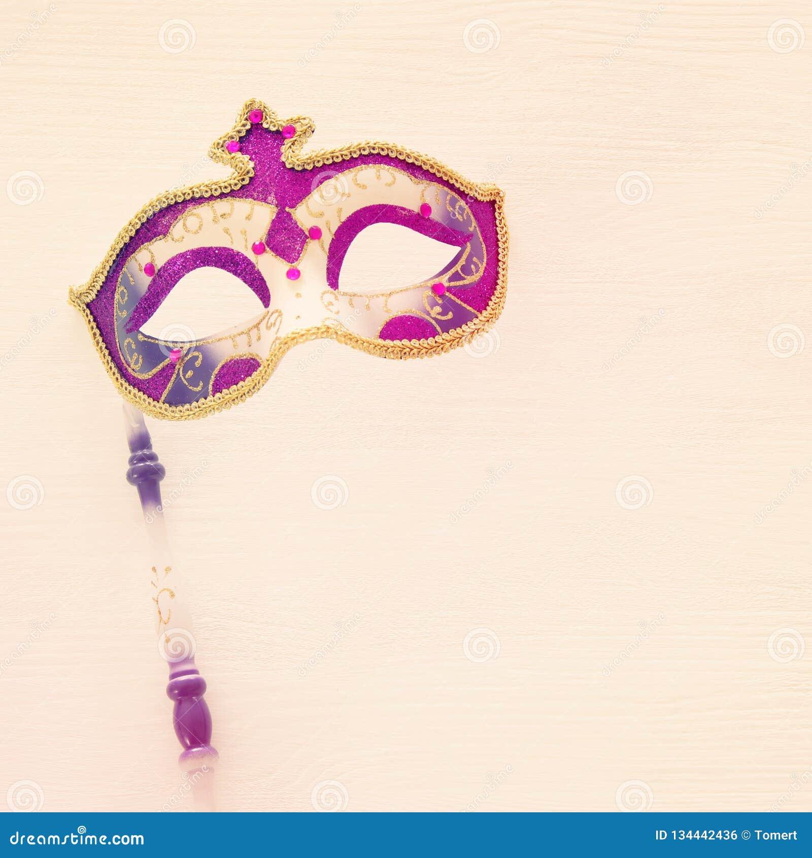Karnawału świętowania partyjny pojęcie z elegancką złota, menchii i purpur maską na kiju nad białym drewnianym tłem, Odgórny wido