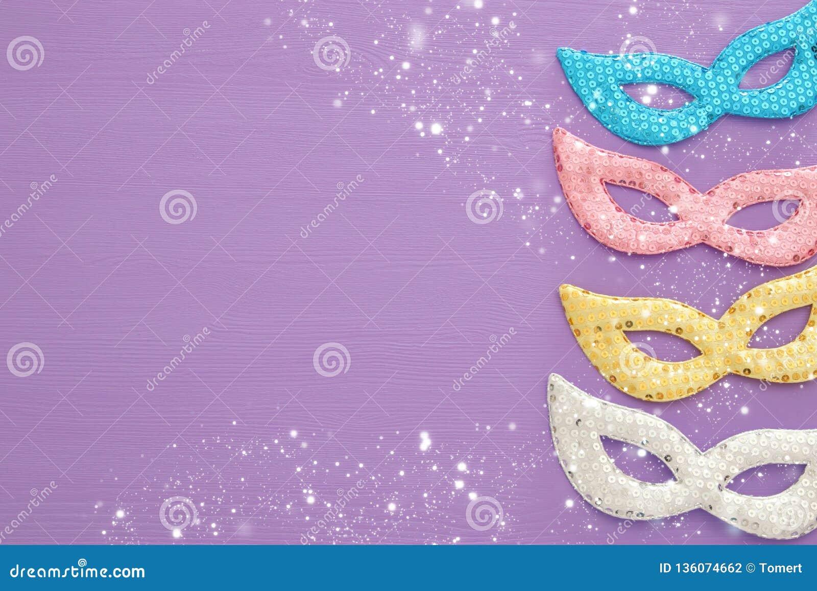 Karnawału świętowania partyjny pojęcie z kolorowymi pastelowych menchii, złota, srebra i błękita maskami nad purpurowym drewniany