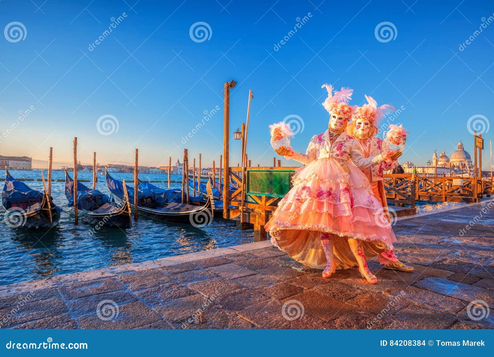 Karnevalmaskeringar mot gondoler i Venedig, Italien