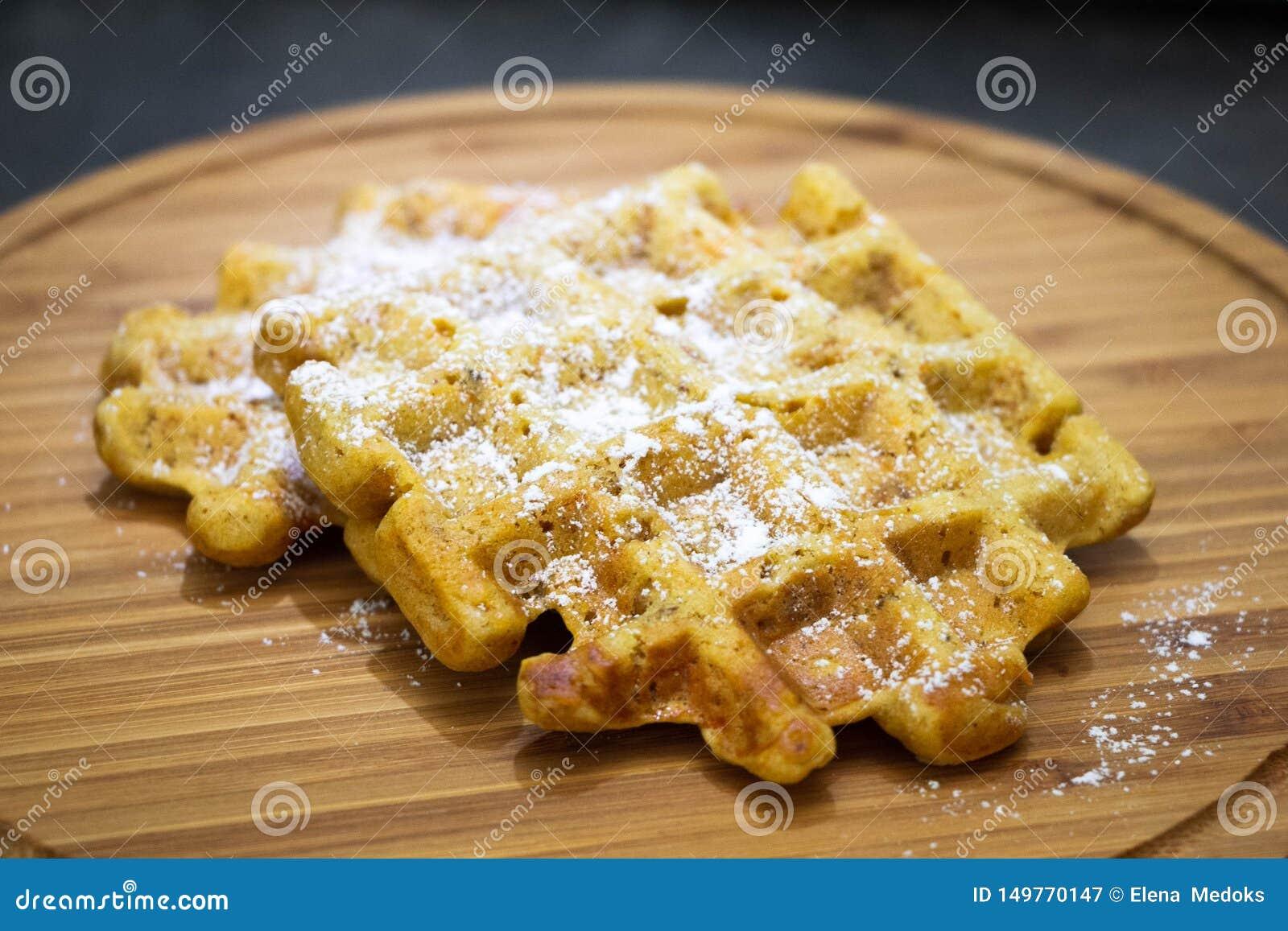Karottenwaffeln mit Puderzucker auf einem hölzernes boardPerfect gesunden Frühstück