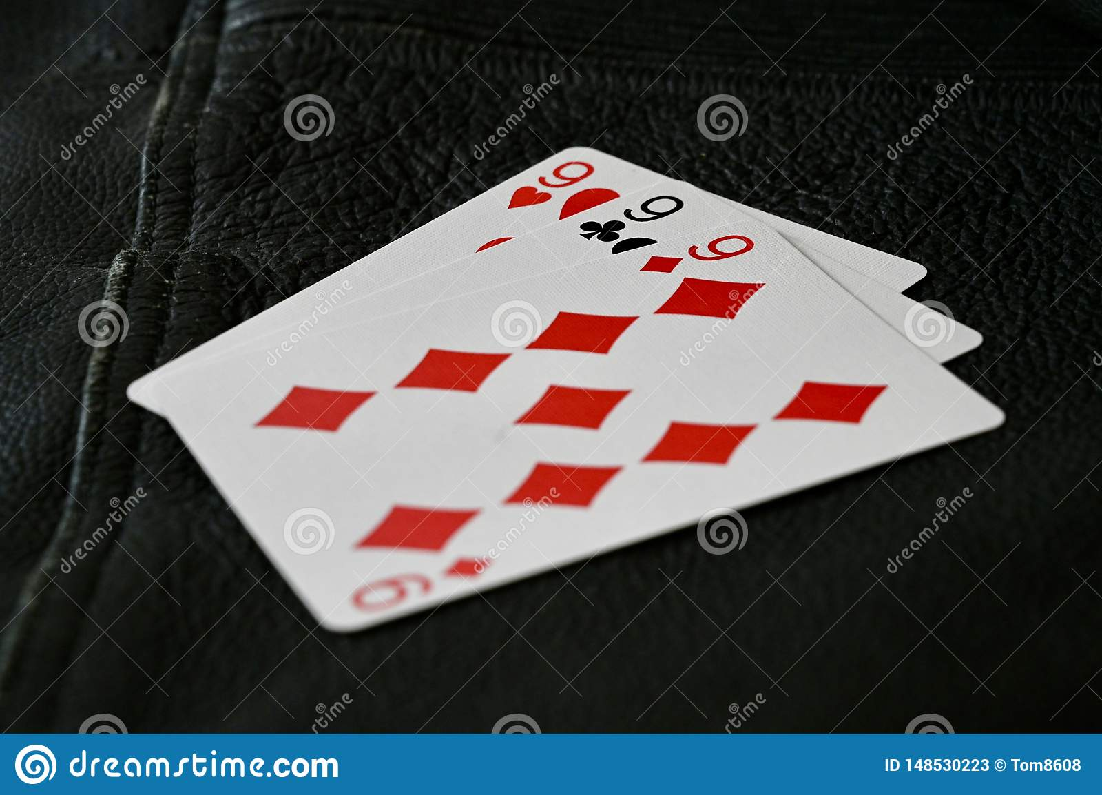 999 Karten-Hand auf schwarzem strukturiertem Hintergrund