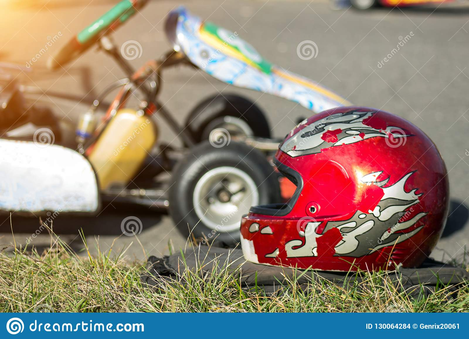 Karting competitions, a red protective helmet lies against the background of the racing carting, close-up