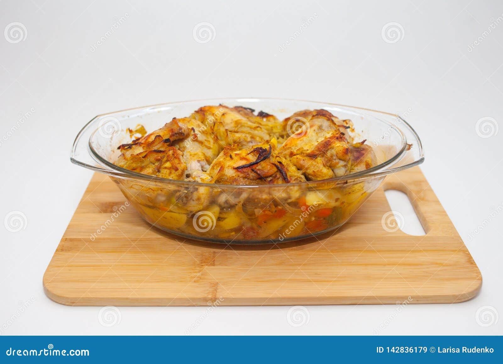 Kartoffeln mit dem Gem?se gebacken im Ofen in einem Glasbeh?lter mit einem Deckel Schneidebrett und wei?er Hintergrund