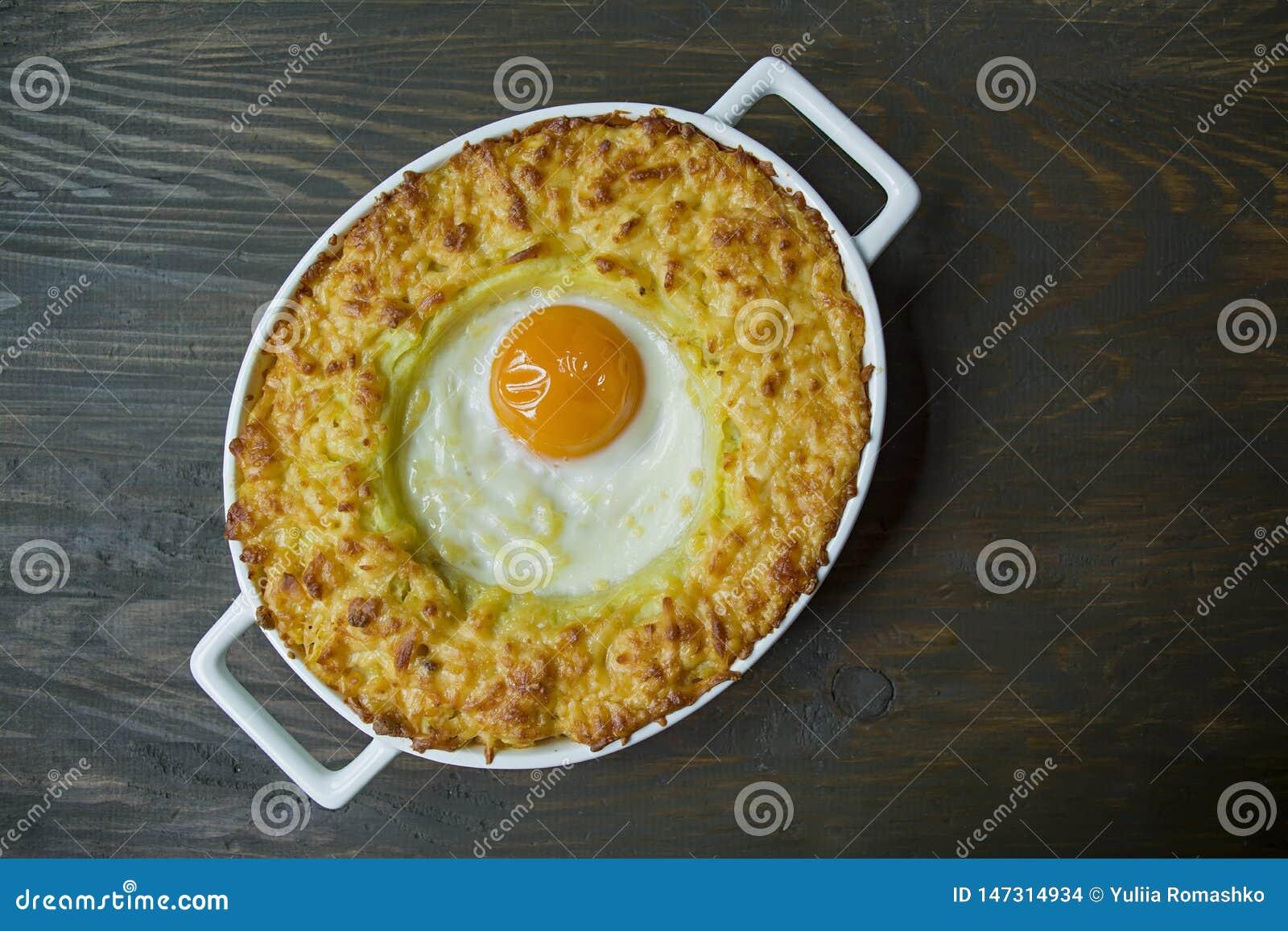 Kartoflana potrawka z Bolognese Piec kartoflana potrawka z jajkiem i kraciastym serem w ceramicznym owalnym wypiekowym prześciera