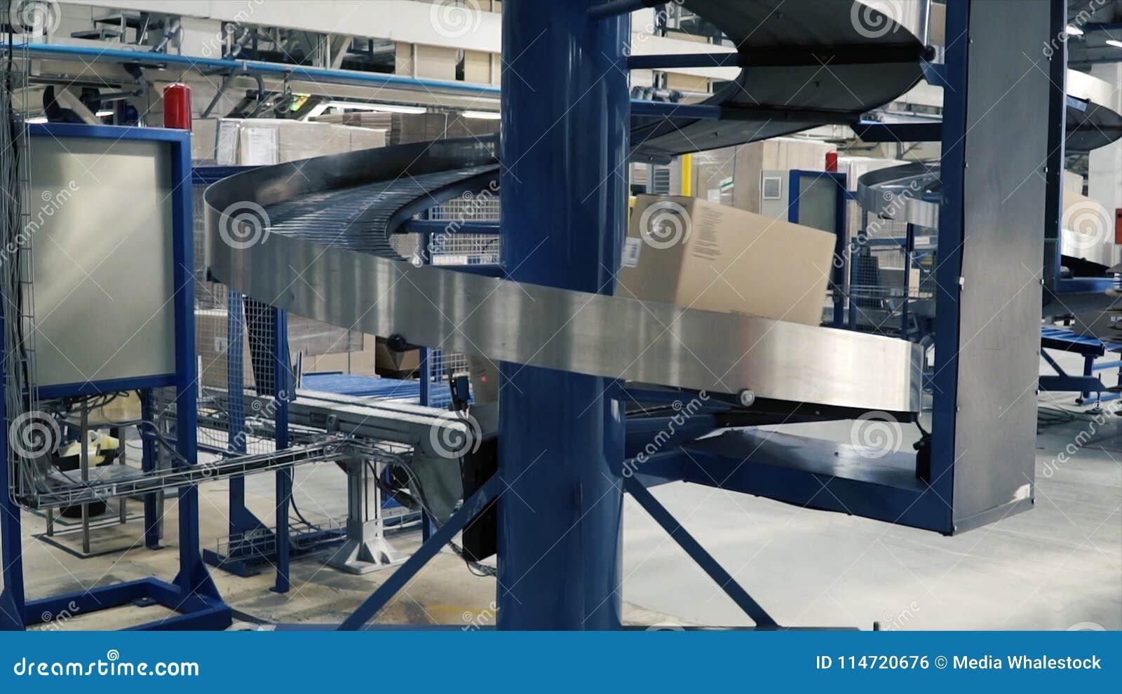 Kartondozen op transportband in fabriek klem Productielijn waarop de dozen zich in een spiraal bewegen