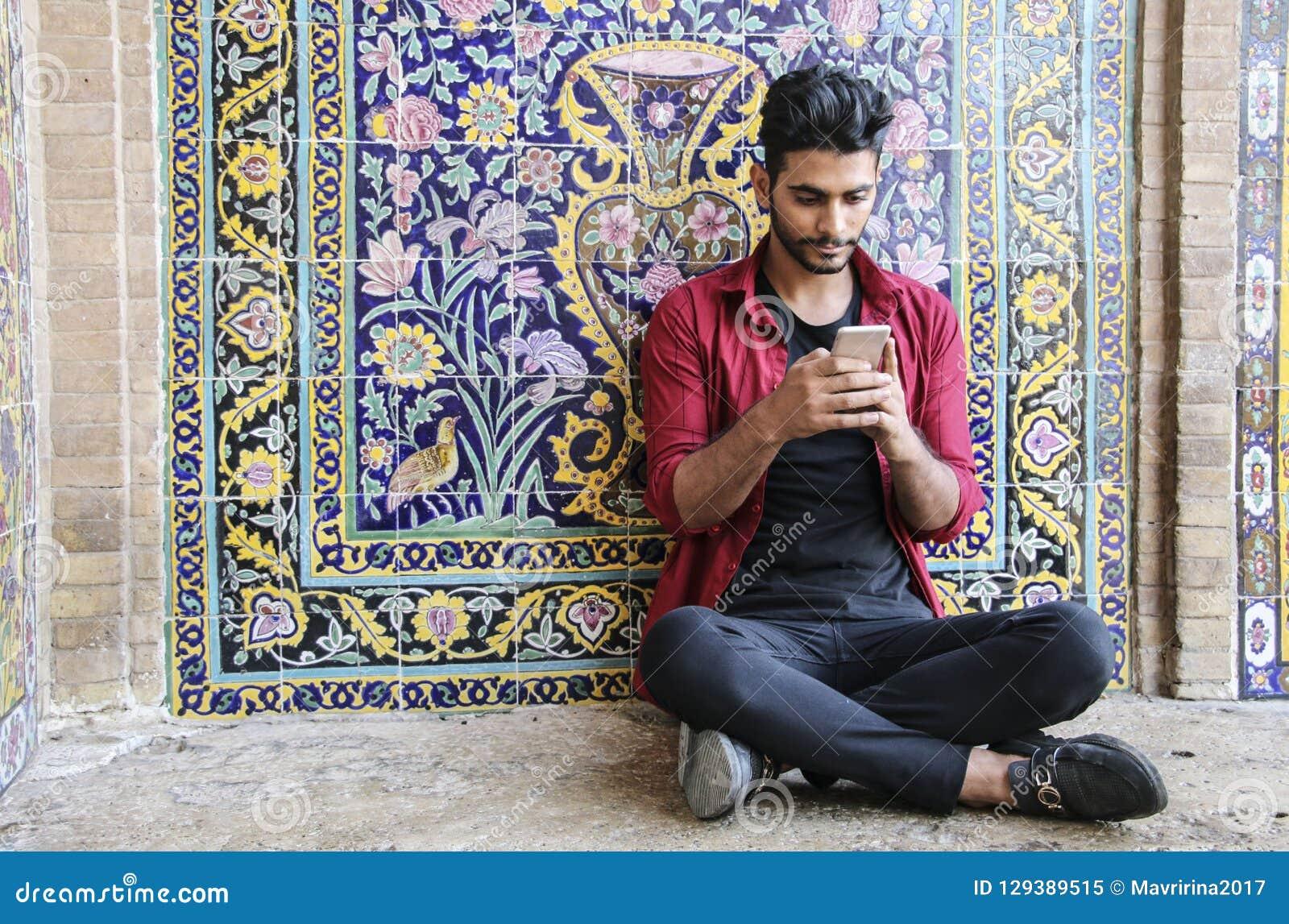 KASHAN, IRAN WRZESIEŃ 23, 2018: Młody Irański mężczyzna siedzi blisko
