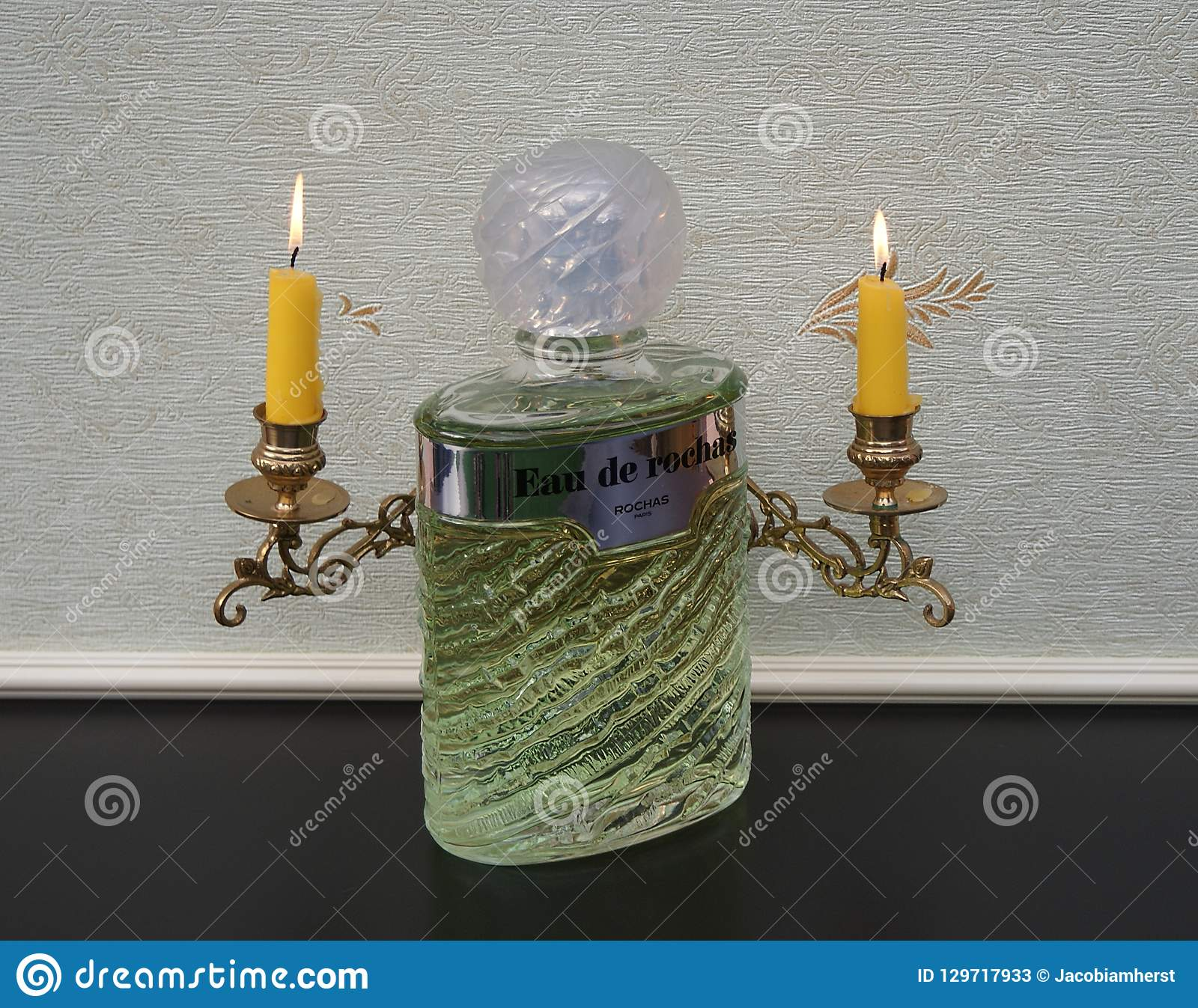 Eau de Rochas, fragrance for ladies, large perfume bottle in front of a piano candelabra with shining candles