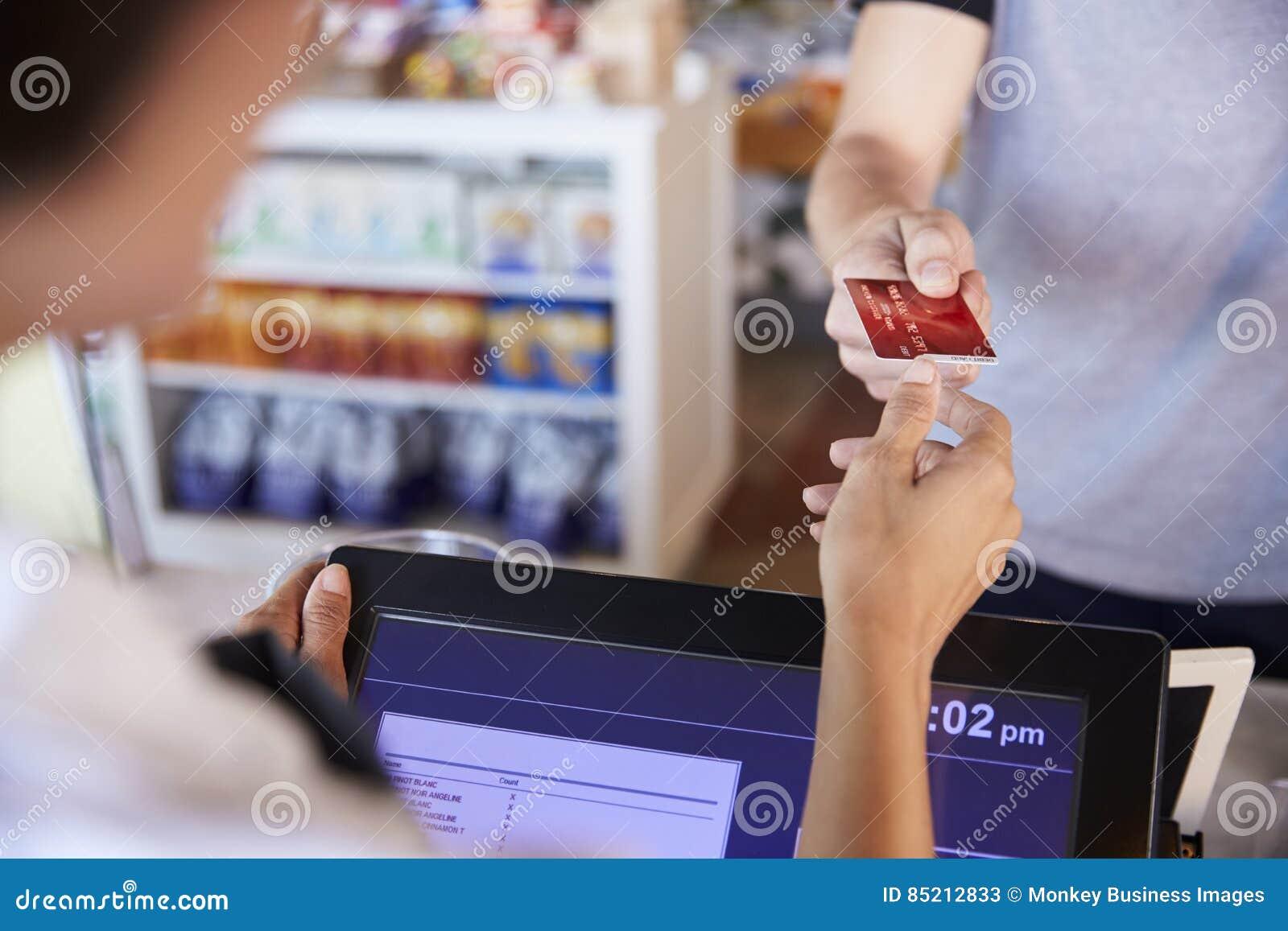 Kassier Accepts Card Payment van Klant in Delicatessen